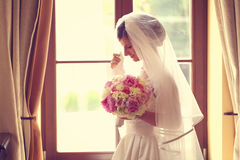 Bride in a hotel room holding her wedding bouquet Stock Photo