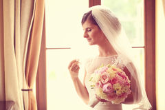 Bride in a hotel room holding her wedding bouquet Stock Images