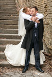 Bride hugging groom from back on stairs Stock Photo