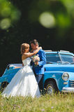 Bride Hugging Groom with Bouquet. At blue car Royalty Free Stock Image