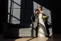 The bride is hugging the groom sitting on the arm of the sofa. They are lit by hard light from the window. Horizontal photo Stock Image