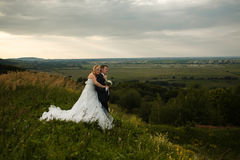 Bride hugs groom from behind while they daydreams on a hill Royalty Free Stock Photography