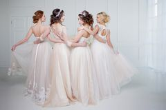 Bride In Wedding Salon. Four Beautiful Girl Are In Each Other`s Arms. Back, Close-up Lace Skirts