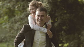 Bride jumping on the back of the groom and laughs stock footage