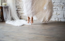 Bride jumping in rustic wedding dress. Bride jumping barefoot in rustic white wedding dress. Beautiful wedding gown. Loft style wedding stock images