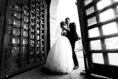 Bride kisses fiance's cheek standing in the open gates Stock Images