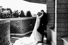 Bride kisses a groom who leans to the wall on the balcony Stock Photography