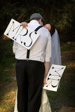 Bride kissing groom. A woman in a bride's dress holding a Mrs sign, kissing a man with Mr. sign Royalty Free Stock Photography