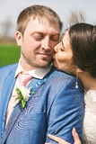 Bride kissing groom to cheek on nature. At sunny day Stock Image