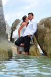 Bride kissing groom - trash the dress - sea scene Stock Photos