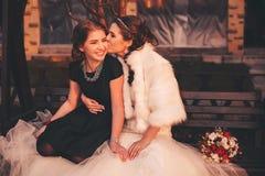 Bride kissing sister to cheek Stock Photos