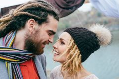 Bride in a knitted hat with pompom and groom with dreadlocks and scarf look at each other with tenderness and love. Close-up portrait Royalty Free Stock Photo