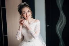 The bride in a lacy white dress and veil is going to the ceremony. Portrait of a girl putting on earrings and smiling. stock images