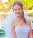 Bride beside a lake. Happy bride in white wedding dress standing  in a park beside a lake Royalty Free Stock Images