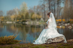 Bride on the lake shore. Bride in a white dress sitting on a rock on the shore of the lake and looks into the distance stock photo
