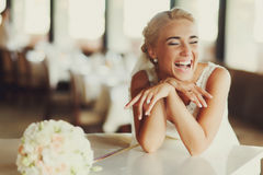 Bride laugh broad sitting at a white piano Royalty Free Stock Photo