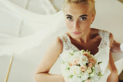 Bride laugh broad sitting at a white piano Royalty Free Stock Images