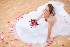 Bride: Laughing Bride On Floor With Petals Around Royalty Free Stock Images
