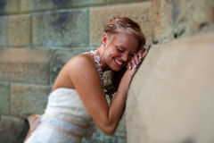 Bride laughing with head resting on hands. A Bride leans against a sandstone building and smiles Stock Photo