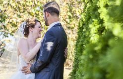 Laughing bride at ourdoor garden wedding. A bride laughing with her groom during an outdoor garden wedding Royalty Free Stock Image