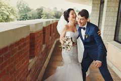 Bride laughs while groom tries to catch her Stock Images