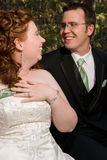 Bride Laugs at Groom's Joke. A young bride laughs at her new groom's joke while placing her hand on her chest Stock Image