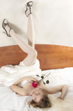 Bride lays on a bed in beautiful white stockings Royalty Free Stock Photo