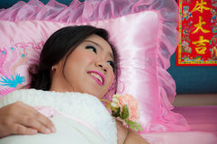 Bride lays on the bed after Chinese marriage Royalty Free Stock Photos