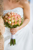 Bride leaning against wall. A vertical close up of a caucasian bride holding a bouquet of pink and yellow roses Stock Images