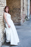 Bride leaning to brick wall Stock Photography