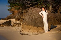 Bride leans against rock on beach Stock Images