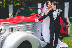 Bride leans on a groom standing on a doorstep of an vintage car Stock Photo