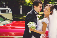 Bride leans on a groom standing on a doorstep of an vintage car Royalty Free Stock Photography
