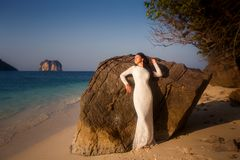 Bride leans on large rock at beach Stock Photography