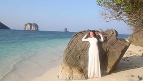 Bride leans on rock at beach against tropical islands stock video