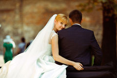 Bride leans to groom's shoulder sitting with him on a retro car stock photos