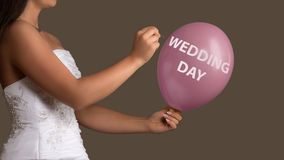 Bride lets a Balloon with Text burst with a needle Royalty Free Stock Image