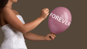 Bride lets a Balloon with Text burst with a needle Stock Images
