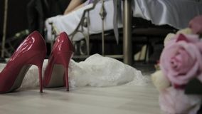 Bride lies on a bed and throws a bouquet on a floor. first wedding night. close-up woman`s shoes and bridal bouquet on a. Close-up woman`s shoes and bridal stock video footage
