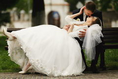 Bride lies on fiance's knees and kisses him Royalty Free Stock Images