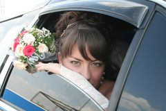 Bride in the limousine. With flowers Stock Images