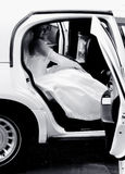 Bride in a limousine. Bride coming out of a limousine Royalty Free Stock Images