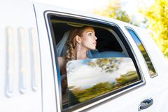 Bride in limousine. Bride looks out of the window a white limousine stock photography