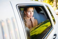 Bride in limousine. Bride looks out of the window a white limousine royalty free stock photo