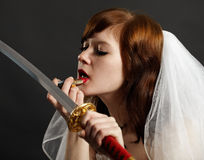 Bride lipstick using reflection in sword Royalty Free Stock Photography