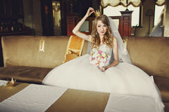 Bride in a little crown sits on a big sofa Stock Photography