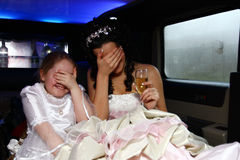 Bride and little girl. Genre scene inside the limousine during the wedding: bride and funny little girl hiding their eyes, becouse they afraid of flash Stock Image