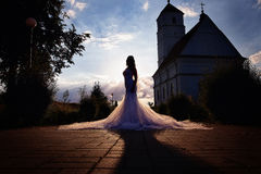 Bride in a long dress near church in the evening stock image