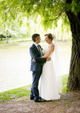 Bride with long hugging with groom under big tree at park Stock Images
