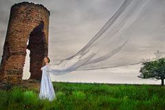 Bride with long veil. Staying against abandoned ruins in the evening Stock Images